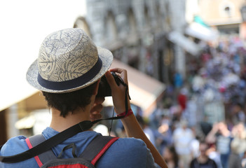 Young photographer with hat on Rialto Bridge in Venice Italy