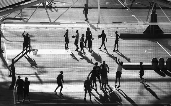 Basketball players silhouettes on Brooklyn pier court at sunset, New York City, USA.
