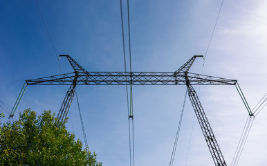 power line tower on a blue sky background. symbol of energy and power