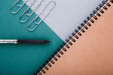 A pencil, a pencil sharpener and crafting notebooks on a green-gray background.