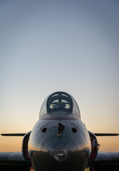 A vintage jet fighter aircraft at sunset with a dusk sky in background, vertical with upper negative space