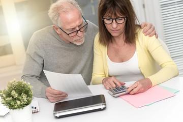 Senior couple checking financial document, light effect