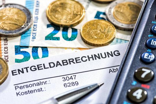 Lohn/Gehaltsabrechnung mit Münzen, Geldscheinen, Taschenrechner und Kugelschreiber