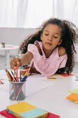 portrait of african american kid taking pencil while drawing colorful picture at table