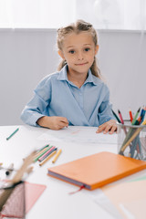 portrait of smiling kid sitting at table with colorful pencils and papers for drawing