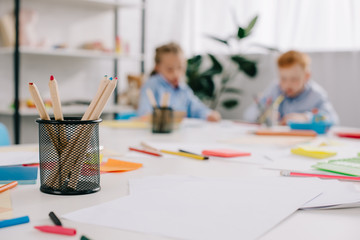selective focus of adorable kids drawing pictures at table in classroom