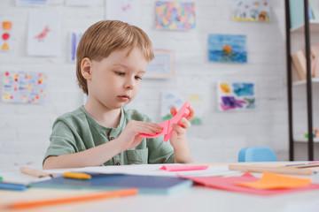 cute preschooler with pink paper sitting at table in classroom