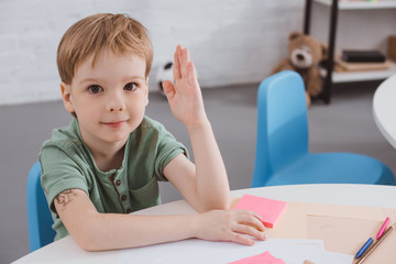portrait of cute preschooler with hand up sitting at table in classroom