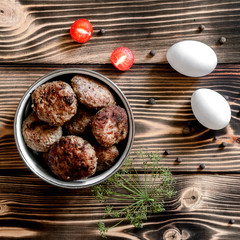 Fried meat patties in a bowl, two eggs and cherry tomatoes on a wooden background with dill branche and allspice. Food concept