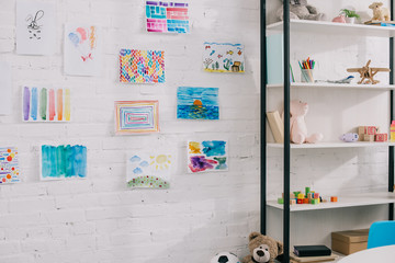 close up view of colorful pictures hanging on white brick wall in classroom