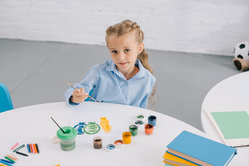 portrait of cute child sitting at table with paints and paint brushes