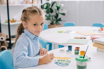 side view of cute child sitting at table with paints and paint brushes