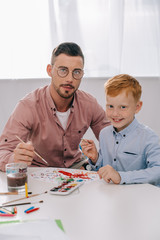 portrait of teacher and little boy with paint brushes sitting at table in classroom