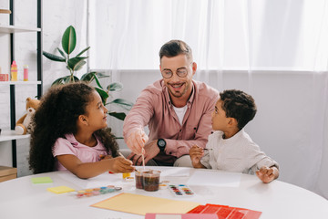 smiling caucasian teacher in eyeglasses and african american kids drawing pictures with paints together in classroom