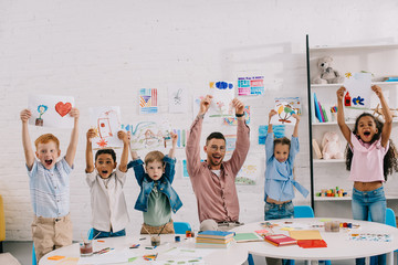 portrait of smiling teacher and multiethnic kids showing pictures in hands in classroom