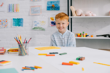 portrait of smiling red hair boy sitting at table with colorful plasticine for sculpturing in room
