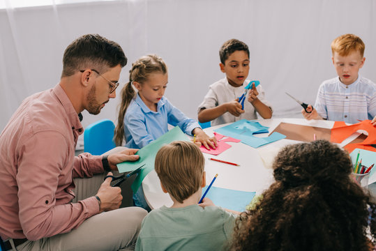 partial view of male teacher and multiracial preschoolers cutting colorful papers with scissors at table in classroom