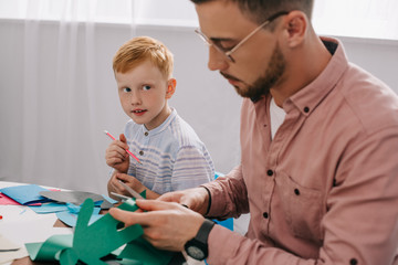 red hair preschooler looking at teacher cutting paper with scissors in classroom