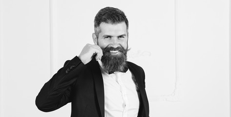 Groom in black classic suit with bow tie on studio. Groom with beard and mustache, smiling holding his mustache. Bearded man in suit with bow tie young elegant stylish. Luxury place. Happy time life.