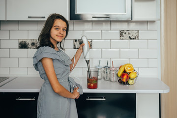 Happy teen girl making fresh juice or meal in a blender in the kitchen. Juice Extractor. Healthy eating concept, vitamins.