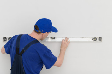 Worker in overalls measures the wall with a level