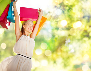 people and sale concept - happy woman with shopping bags over green background and lights