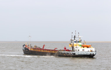 Sand dredging boat drawing away from coast shoreline to pump sand