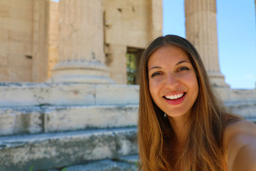 Smiling young woman taking selfie photo on the Acropolis with greek temple on the background, Athens, Greece
