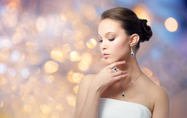 beauty, jewelry, people and luxury concept - beautiful asian woman or bride with earring and pendant over holidays lights background