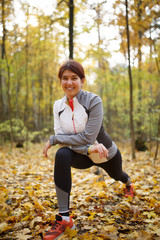 Autumn photo of sporty woman stretching in forest at morning against background of trees