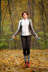 Full-length image of young girl jumping with rope at autumn forest