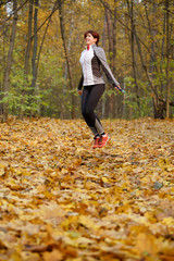 Full-length photo of female athlete jumping with rope at autumn forest