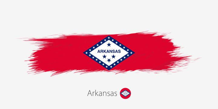 Flag of Arkansas US State, grunge abstract brush stroke on gray background.