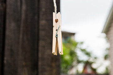 wooden clothespins hang on a rope on a wooden background