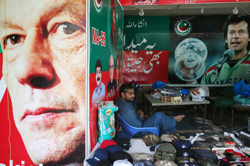 A vendor sits next to images of cricket star-turned-politician Imran Khan, chairman of Pakistan Tehreek-e-Insaf (PTI) at a market in Islamabad
