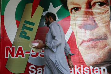 A man walks past an image of cricket star-turned-politician Imran Khan, chairman of Pakistan Tehreek-e-Insaf (PTI) at a market in Islamabad