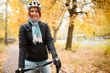 Image of smiling woman in helmet on bicycle