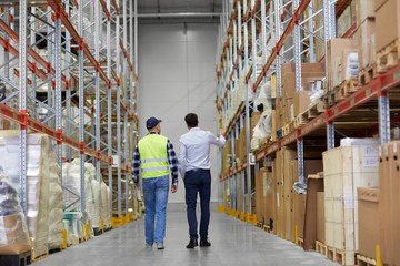 logistic business, shipment and people concept - rear view of businessman and worker walking along warehouse