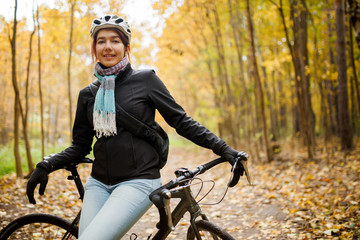 Portrait of brunette in helmet, jeans next to bicycle in autumn park