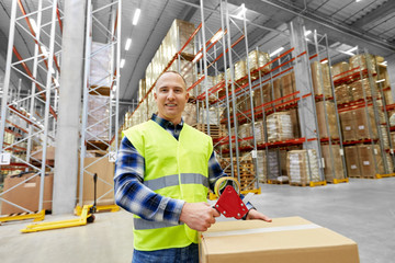 logistic business, shipment and people concept - worker in safety vest packing parcel box with scotch tape at warehouse or mail storage