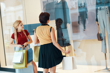Young stylish women with paper bags standing in front of window case of store and looking at mannequins