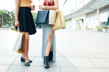 Faceless shot of fashionable women holding drinks in cups and carrying paper bags while standing on street