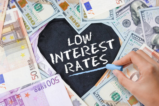 Low interest rate at mortgage loans, credit card or other types of loans, text in heart shape from cash banknotes in various currencies