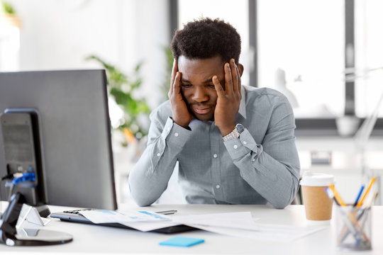 business, people, deadline and technology concept - stressed african american businessman with papers and computer working computer at office