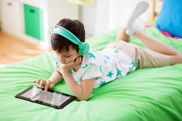 childhood, technology and people concept - boy with tablet pc computer and headphones lying on bed at home