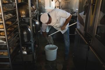 Male baker cleaning floor with floor mop