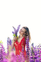 Portrait of a beautiful girl in a field of lupines