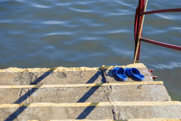 Standing on the wooden flooring near the river is summer shoes: flip flops..