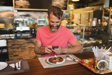 Man using mobile phone in bakery shop