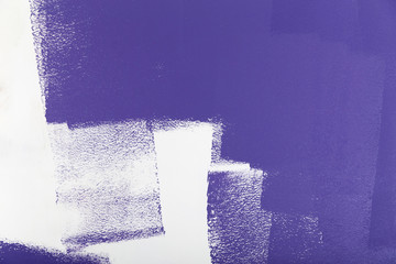 Violet paint roller on a white wall